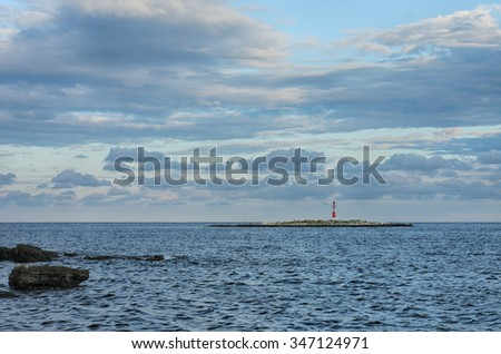 Red lighthouse on small island, on background cloudy sky.