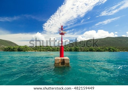 Red lighthouse on the background of the blue Sea, sunny summer day