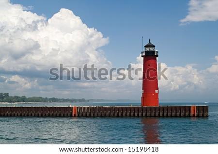 Red lighthouse under dramatic blue and white sky in Kenosha, Wisconsin; Lake Michigan - stock photo