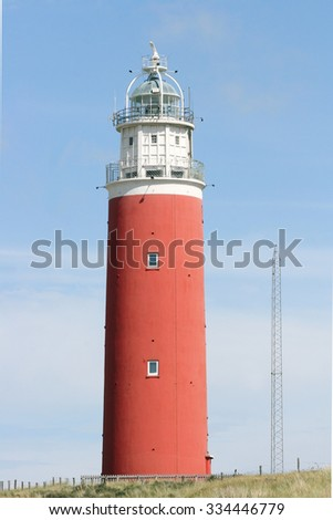 red lighthouse with blue sky in the background
