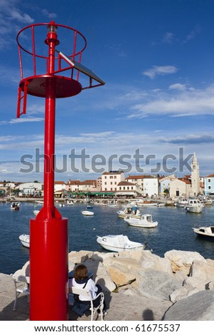 Red lighthouse with solar panel and woman sitting on bench in harbor of Fazana in Croatia - stock photo
