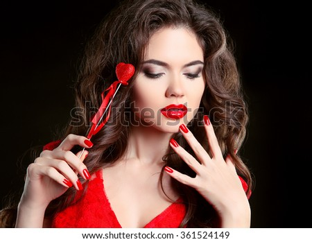 Red lips, manicured nails. Beautiful young woman model with beauty makeup, curly hairstyle, polish manicure. Brunette girl with heart isolated on black background, Valentine day. - stock photo