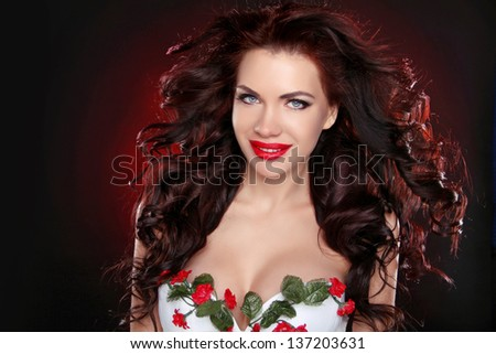 Red Lips. Portrait of sexy brunette girl with professional make-up and hairstyle over dark background - stock photo