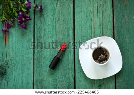 Red Lipstick and cup of coffee on wooden table decorated violet flowers and berries - stock photo