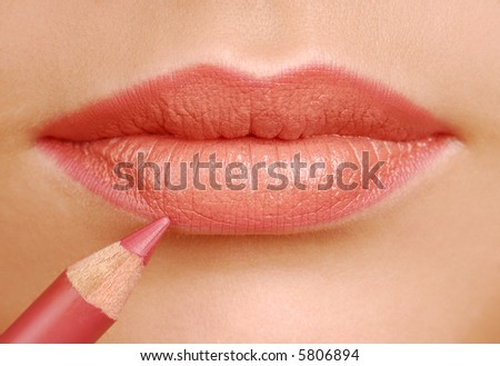 Red lipstick cosmetic pencil. Make-up tool. Woman lips close up