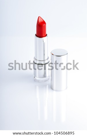 Red lipstick in silver metal tube over white reflective background - stock photo