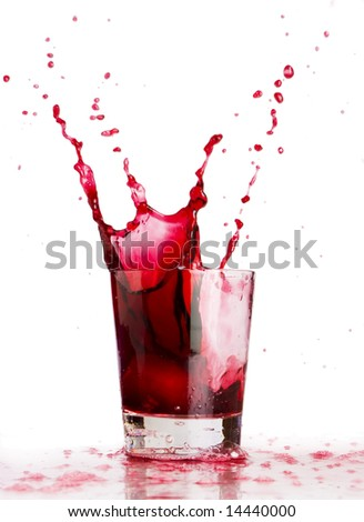 Red liquid splash, Ice cube dropped into a glass of grape juice - stock photo