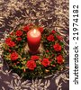 red lit candle surrounded by red and green decoration on a table top - stock photo