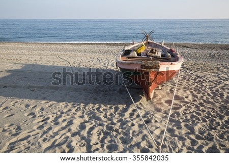 Red Little Fishing Boat on the Beach near the Sea