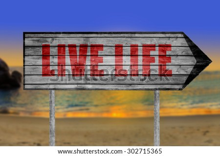 Red Live Life wooden sign with a beach on background