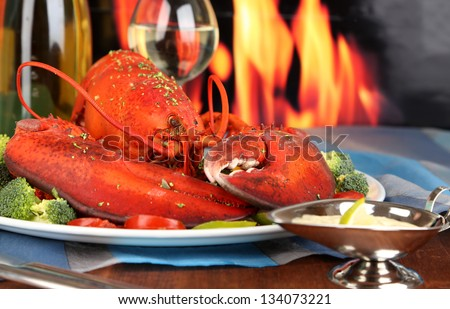 Red lobster on platter on wooden table on fire background - stock photo