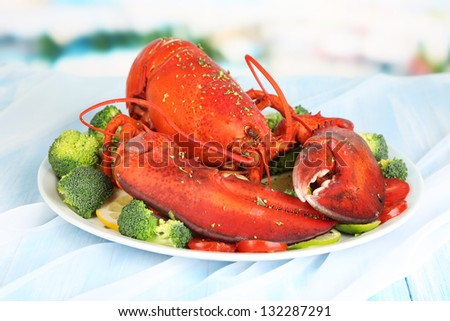 Red lobster on platter with vegetables on table close-up
