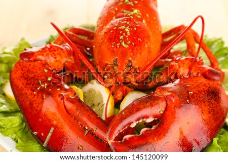 Red lobster on platter with vegetables on wooden table close-up - stock photo