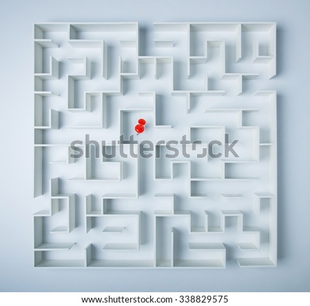 Red location direction pin in the middle of a maze, a symbol of searching for success - stock photo