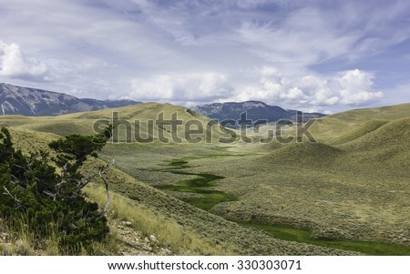 Red Lodge, Montana, USA - The Beartooth Mountains and foothills with a valley flanked by shrub land near Red Lodge, Montana, USA. - stock photo