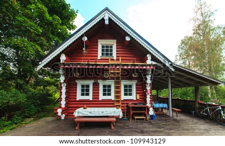 Red Log Cabin Holiday Home in the Forest - stock photo