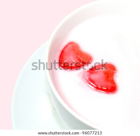Red Love Hearts In Milk-Two red love hearts floating in milk on a pink background.