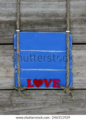 Red Love text on blank antique blue wooden sign hanging by braided rope on rustic shabby wood background - stock photo