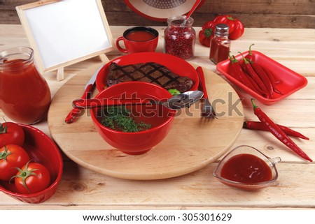 red lunch fresh grilled bbq roast beef steak plate green tomato soup ketchup sauce jug glass ground pepper american peppercorn modern cutlery served wooden plate table empty nameplate menu board - stock photo