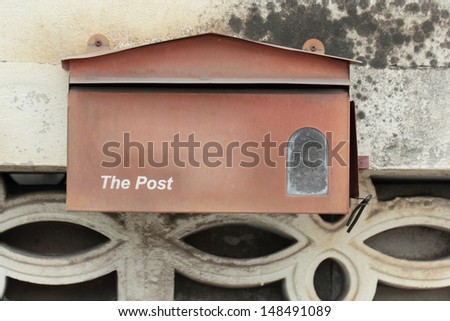 red mail box hang on the rock background - stock photo