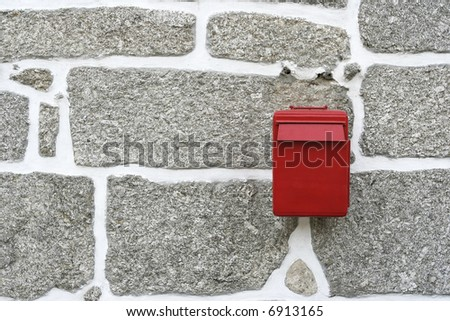 red mail box in a stone wall - stock photo