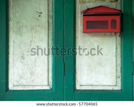 red mail box on green wood door