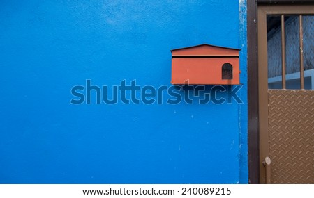 Red mail box on the blue concrete wall  - stock photo