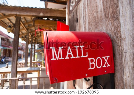 Red mail box on wooden wall in old town - stock photo