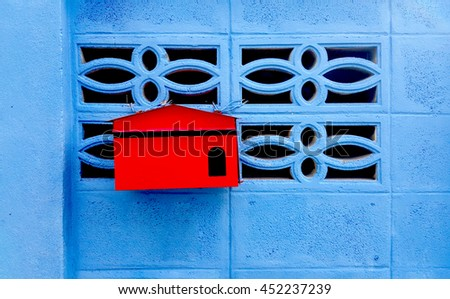 Red mailbox on blue wall. Post Box red on a blue background. - stock photo