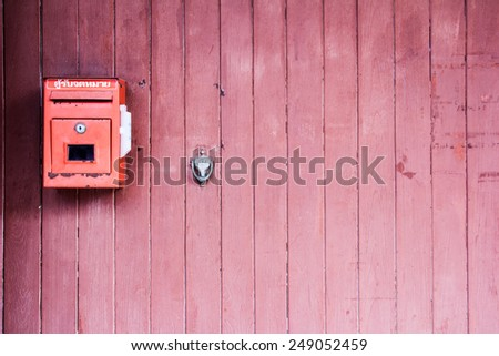 Red mailbox on the red wooden door - stock photo