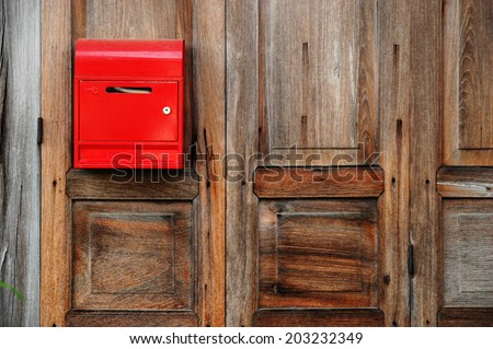 Red mailbox on the wooden door - stock photo