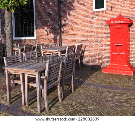 Red mailbox, wooden tables and chairs on the ancient street. Europe, Netherlands