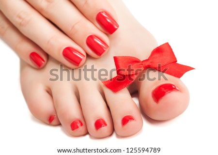Red manicure and pedicure with a bow - stock photo