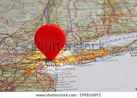 Red map pointer stuck into of New York - stock photo