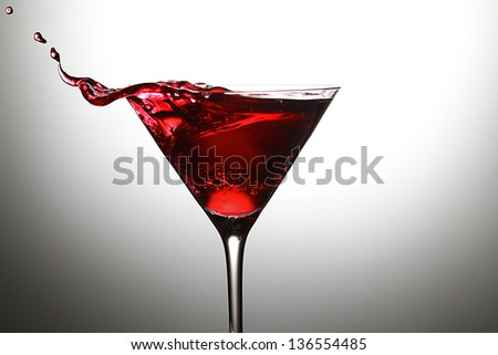 red martini cocktail splashing into glass - stock photo