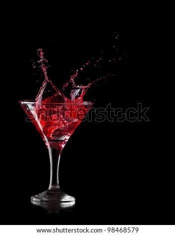 red martini cocktail splashing into glass on black background - stock photo