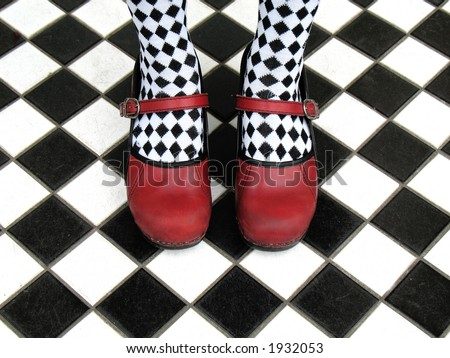 Red Mary Jane shoes worn with black and white checkered tights on checkered tile floor