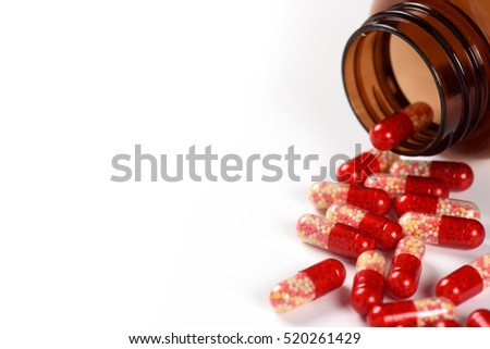 red medical capsules and bottle isolated on white background