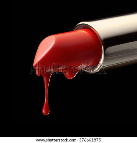 Red melting lipstick isolated on black background with drips on it