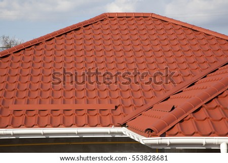 Red metal tile roof of a house against blue sky background
