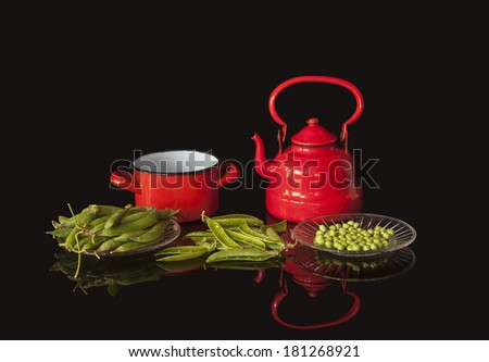 Red metal utensils and peas on the table - stock photo