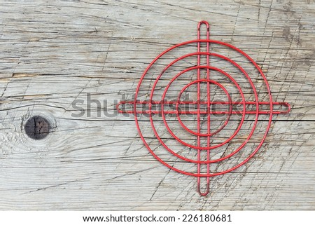 Red metallic crosshair on an old wooden surface. Sight - stock photo