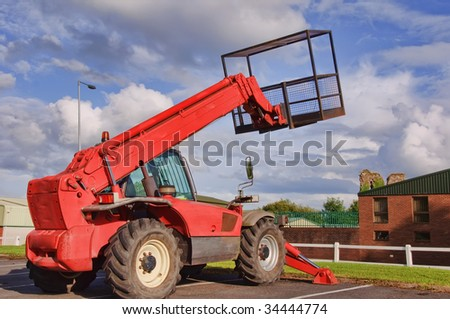 red mobile cherry picker into blue sky - stock photo