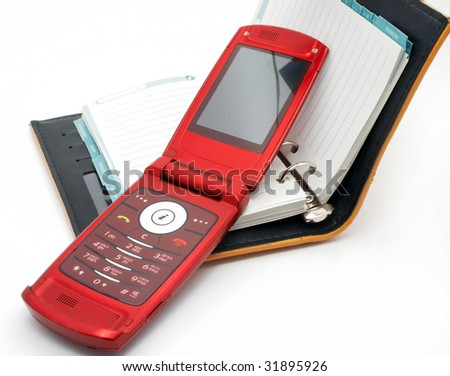 Red mobile phone on an open notebook
