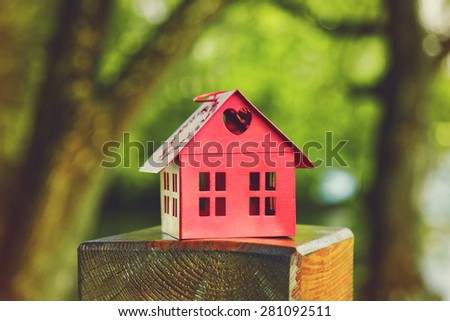 red model of house as symbol on natural garden background - stock photo