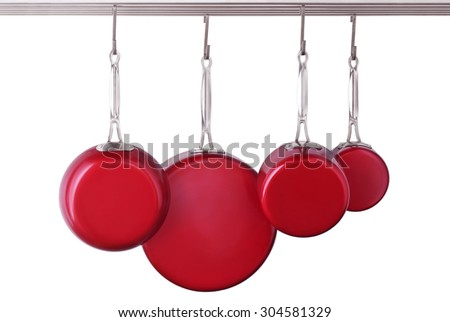 Red, modern skillets and pans on white background - stock photo