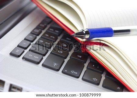 Red moleskine calendar or organizer or notebook and pen on the laptop - stock photo