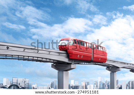Red monorail train against blue sky and modern city in background - stock photo