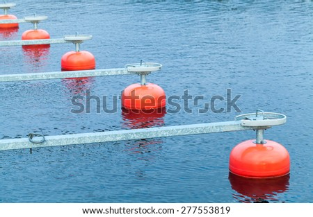 Red mooring buoys in a row floating on blue water, small European yacht club, marina port fragment - stock photo