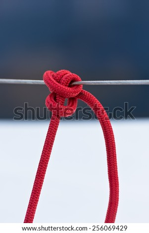 Red mooring rope tied around a lifeline. Vertical shot - stock photo